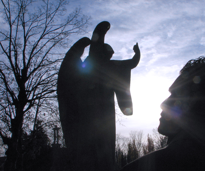 Silhouettes of a man and an angel's statue, against the light of the sun.